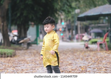 The boy in traditional Vietnamese costume plays along the road with beautiful trees at sunset in Hanoi, Vietnam. date 04/03/2018