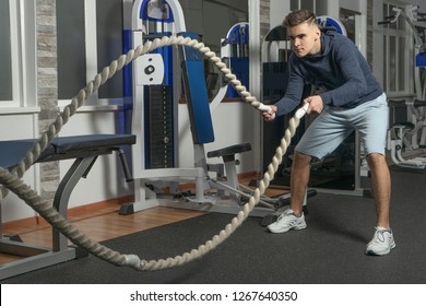 A boy is training with battle rope in gym