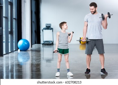 Boy training with dumbbells together with coach at fitness center
