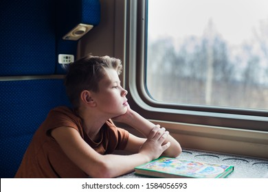 boy traveling by train, look at window