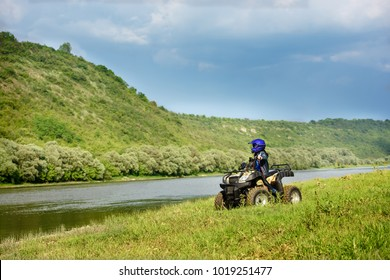 The boy is traveling on an ATV.