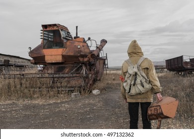 Boy traveling on foot in a post-apocalyptic world in search of water and food. Nomad boy inspects an abandoned combine harvester to find the necessary items for survival. post-apocalyptic world.