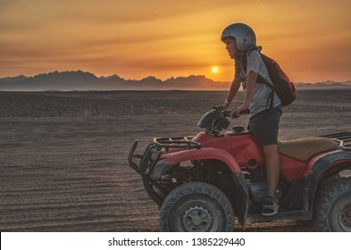 Boy travels on an ATV in the desert at sunset