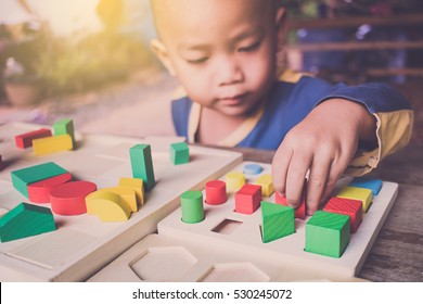 Boy try to do question with wooden color blocks. concept education.