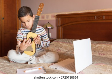 The boy try to learning the timple lesson at home from the internet with his smart phone.  The timple is a typical musical instrument from the Canary Islands, Spain