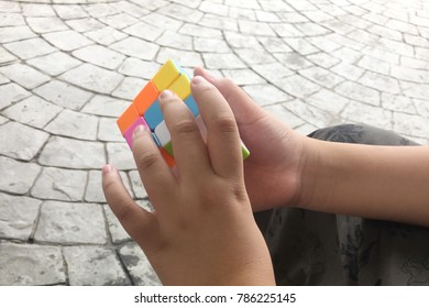 A boy trying to solving the 3 by 3 rubic cube