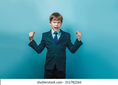 a boy of twelve European appearance in a suit shouting angry  on  a  gray  background