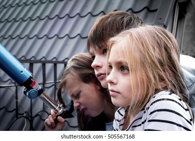 boy and two girls in front of a telescope on  tiled roof