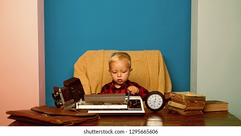 Boy typewrite special report on vintage typewriter. Little photojournalist work on written report at office desk.