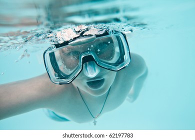 boy under water in pool on a blue background