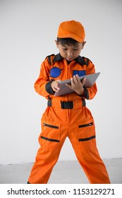 A boy uniform as a astronout browsing with tablet on white background