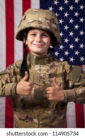 Boy USA soldier is showing thumbs up in front of American flag. Young boy dressed like a soldier