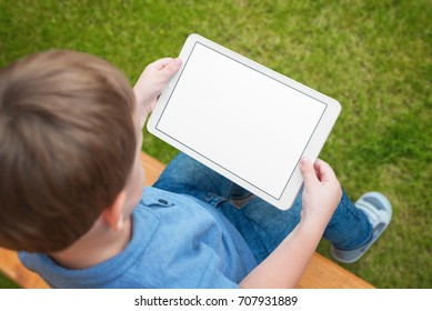 Boy use tablet with isolated white screen for mockup. Child playing game, surfing or watching cartoon.