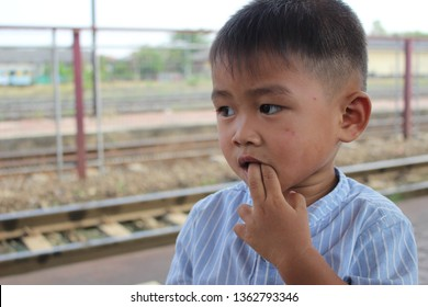The boy uses his fingers to poke into his mouth