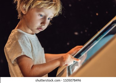 The boy uses the touch screen in the dark.