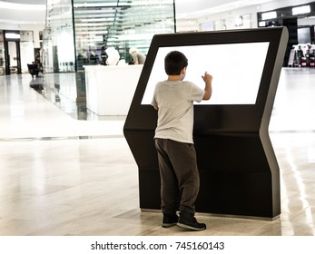 A boy using digital media blank black and white screen modern panel, signboard for advertisement design in a shopping center, gallery. Mockup, mock-up, mock up with blurred background, digital kiosk.