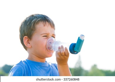 Boy using inhaler for asthma in village with summer sunset