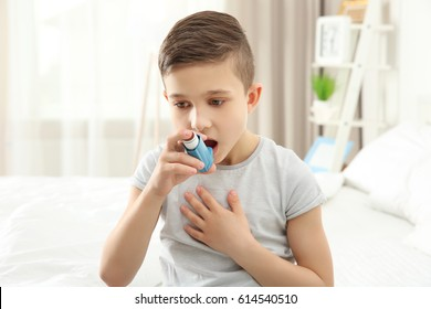 Boy using inhaler during asthmatic attack at home
