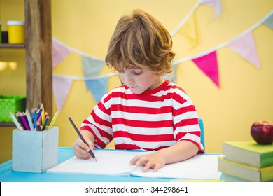 Boy using a pencil to write on paper at the desk