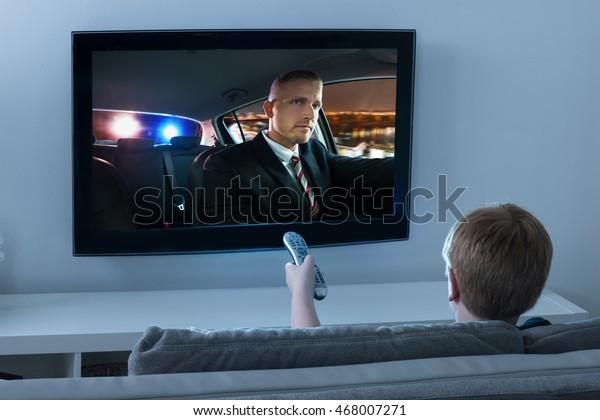 Chlapec pomocí dálkového ovládání při sledování filmu v televizi doma