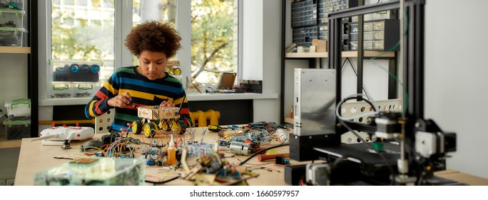 Boy using screwdriver while fixing bolts on a robot vehicle. Smart kids and STEM education. Robotics and software engineering for elementary students. Web Banner - Shutterstock ID 1660597957