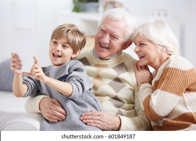 Boy using tablet device, taking selfie with grandparents