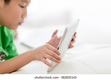 Boy using tablet at home, selective focus at tablet with copy space for text.