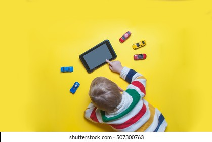 Boy using tablet and laptop while playing with toy cars on a carpet at home. Modern family. Tablet pc hero header image. Boy using digital tablet while lying on yellow floor.