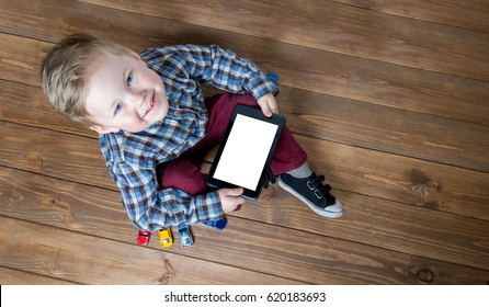 Boy using tablet and laptop while playing with toy cars on wooden floor at home. Tablet pc hero header image. Boy using ipad while lying on floor.