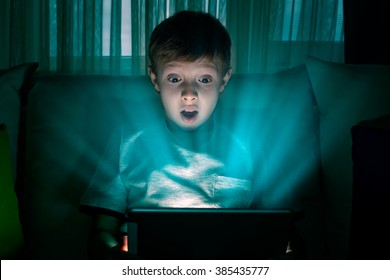 Boy using tablet pc at night. Boy with tablet computer in a dark room.