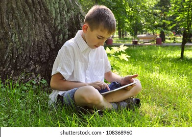 boy using tablet pc outdoor in summer park