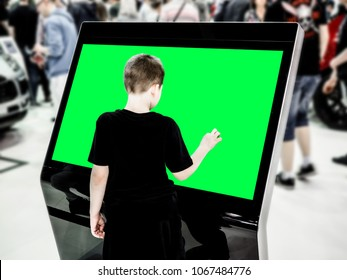 A boy using touch screen mock up of kiosk digital stand, for ads, marketing advertising, design, promotion in the shopping centre, gallery, convention centre, events.