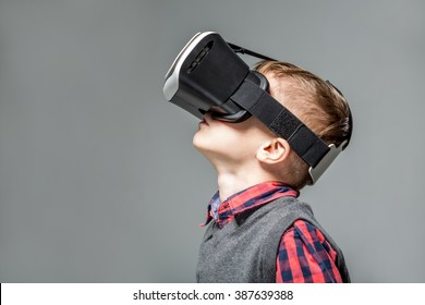 Boy in virtual reality glasses playing the game, focus on face