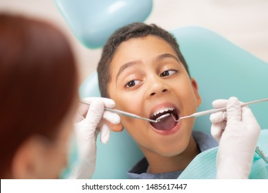 Boy visiting dentist. Handsome dark-skinned boy opening mouth while visiting dentist