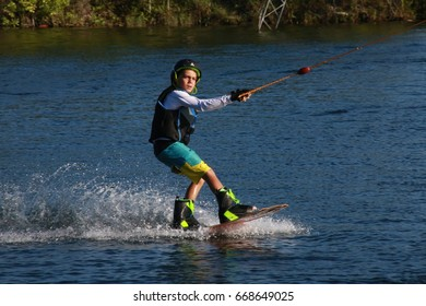 Boy Wake Boarder Being Pulled by Cable in the Late Afternoon Sun at Quiet Waters Park Lake in Deerfield Beach, Florida on June 22, 2017