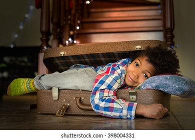 Boy waking up inside suitcase. Afro kid's energetic morning smile. New day new journey. Time for adventures.