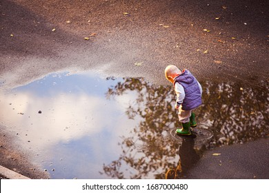 Boy walk in the puddle after the rain