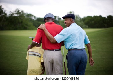 Boy walking across golf course with Father and Grandfather