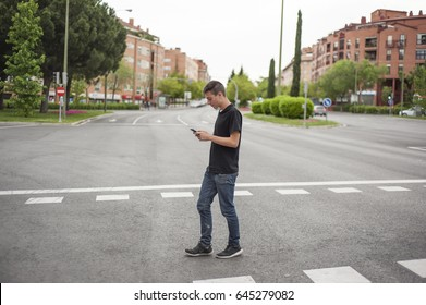 Boy walking by a pedestrian crossing with the phone