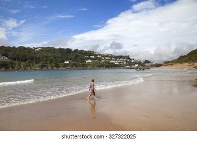 Boy walking on beach at Salcombe, Devon, England