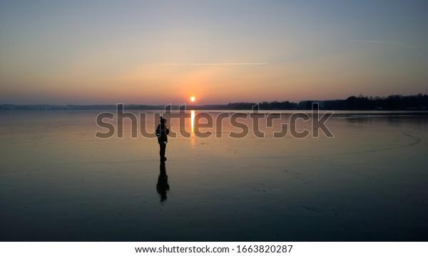 Boy walking on frozen Lake Woerthsee at sunset, Bavaria, Germany, Europe