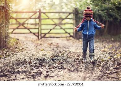 Boy walking on muddy footpath in autumn at sunset