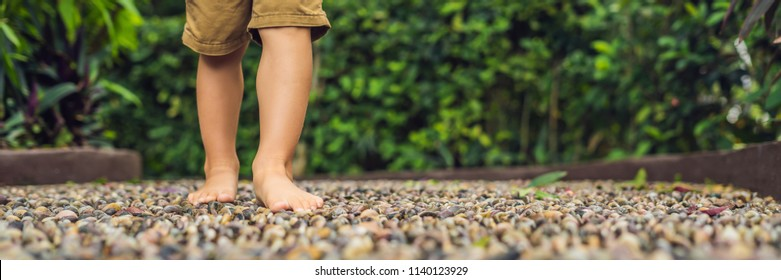 Boy Walking On A Textured Cobble Pavement, Reflexology. Pebble stones on the pavement for foot reflexology. BANNER long format