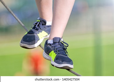 boy walking on tightrope closeup front view of kid feet in sneakers on steel rope against blurred background sport outdoor hiking activity authentic lifestyle concept natural color photo