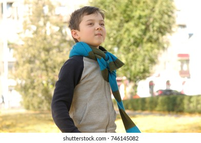 Boy walking in the park on a joyful sense of freedom. A long scarf is tied around the boy's neck