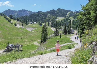 Boy walking with view to the mountain Vogel Ski Resort in Slovenia in summer