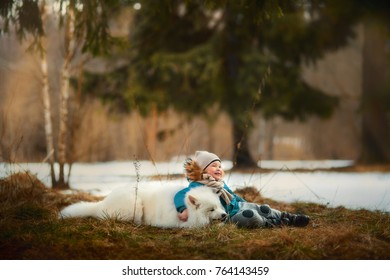 Boy walking with white Samoyed dog at winter forest
