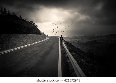 A boy walks down a lonely road toward a light horizon
