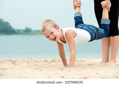 The boy walks in his arms on the sand on the beach. Active rest.