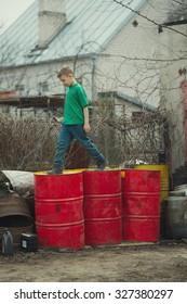boy walks on barrels from the oil